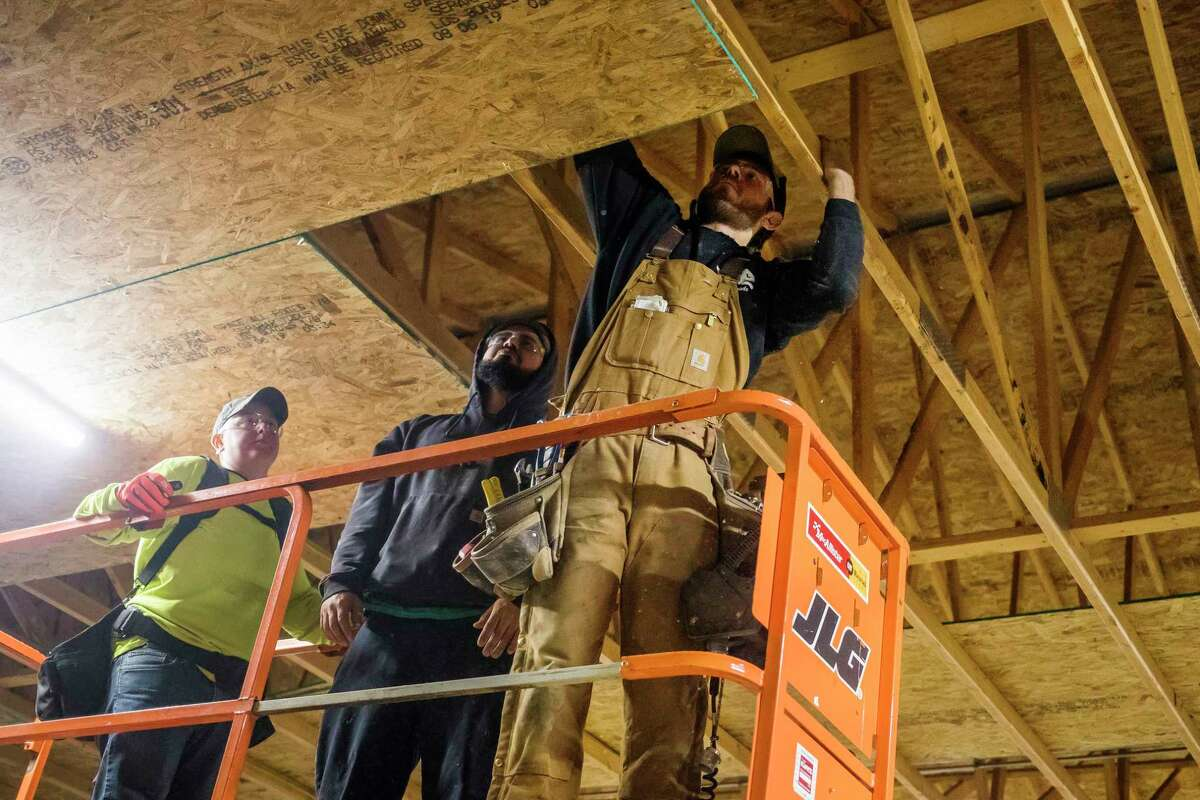 A group of builders from Greater Midland Construction Academy work to install insulation Monday in a pole barn at Messiah Lutheran Church, which is used by The Bridge Food Center. (Katy Kildee/kkildee@mdn.net)