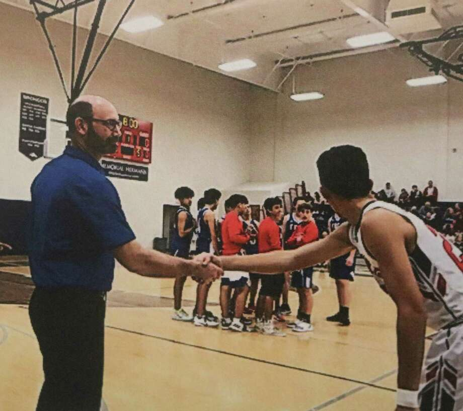 Pasadena-FBCA boys head coach Mike Ritthaler shakes hands with a Bay Area Christian player during starting lineup introductions Tuesday night in the Broncos Field House. Photo: Robert Avery