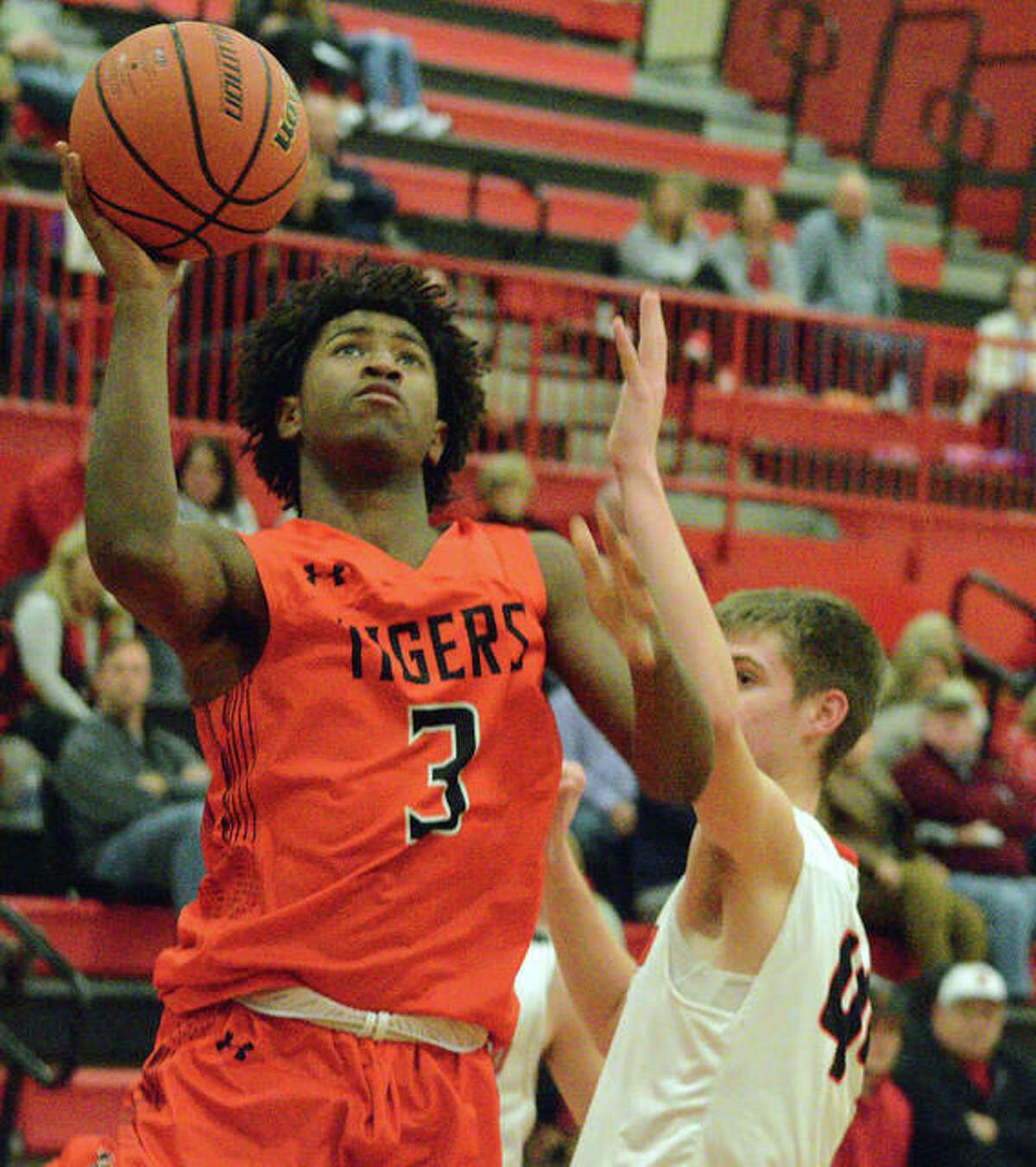 Edwardsville's Gabe James, left, goes up for a layup during Tuesday's game at Highland.