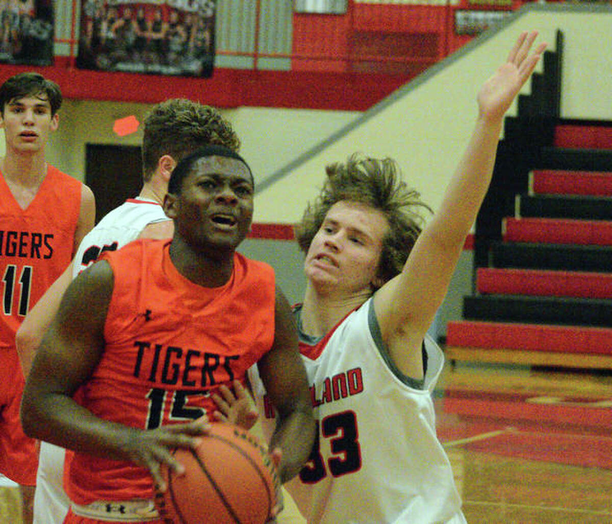 Edwardsville's Willie Thomas, left, drives to the basket during Tuesday's game at Highland.