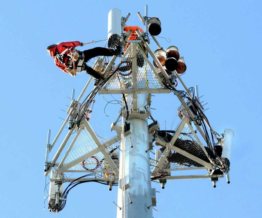 Tchnicians work on a cell tower in Guilford, Conn. Photo: Mara Lavitt / New Haven Register / Mara Lavitt