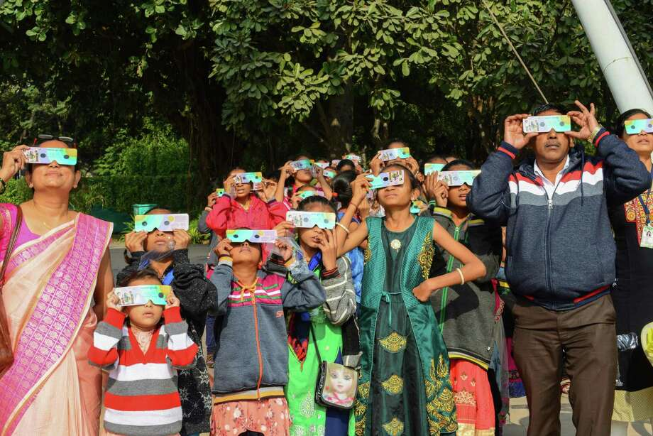 TOPSHOT - Students and teachers use solar filter glasses to look at the solar eclipse at Gujarat Science City on the outskirts of Ahmedabad on December 26, 2019. (Photo by SAM PANTHAKY / AFP) (Photo by SAM PANTHAKY/AFP via Getty Images) Photo: SAM PANTHAKY / AFP Via Getty Images / AFP or licensors
