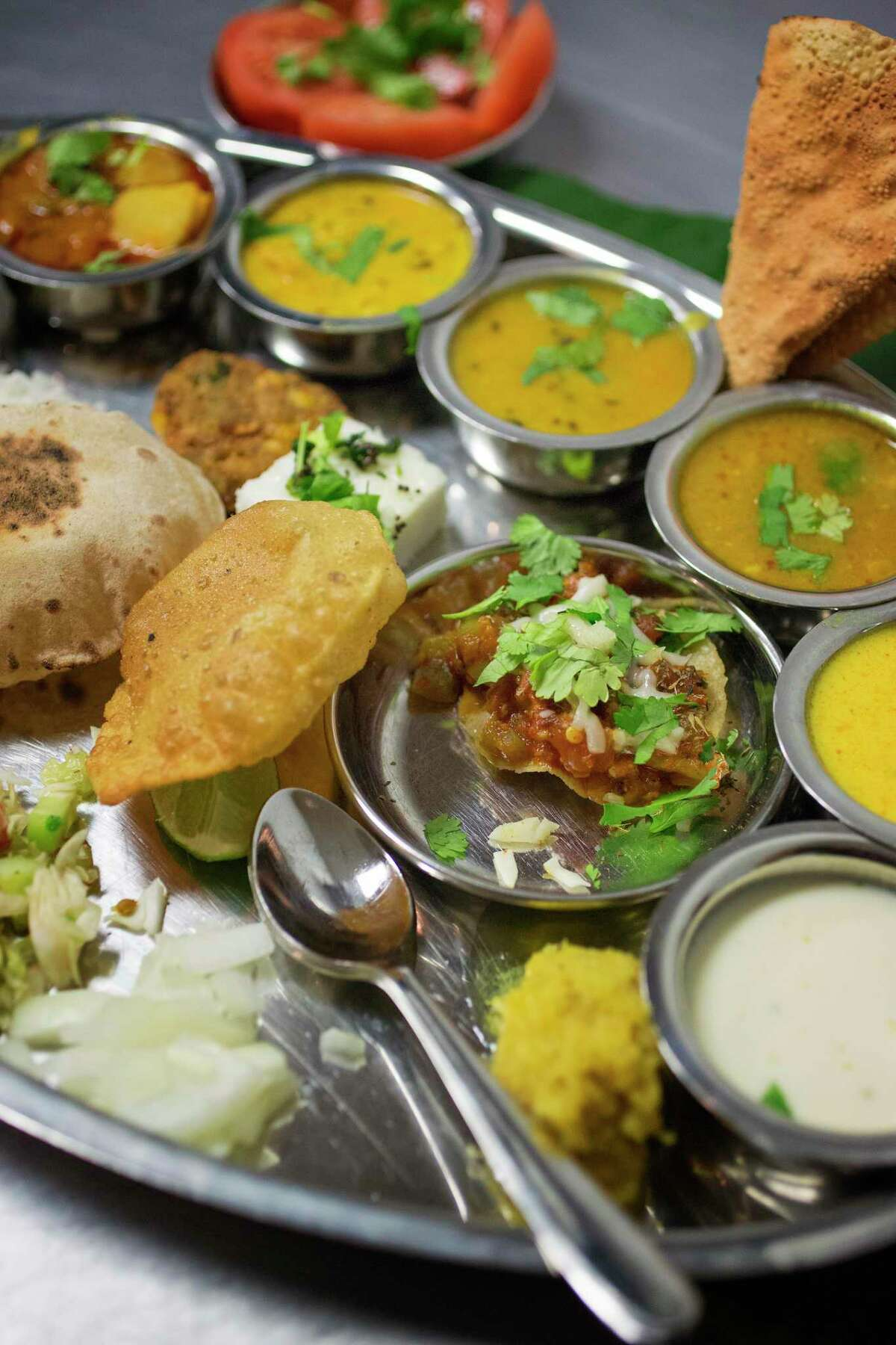 A traditional Indian vegetable thali is shown at Maharaja Bhog restaurant.