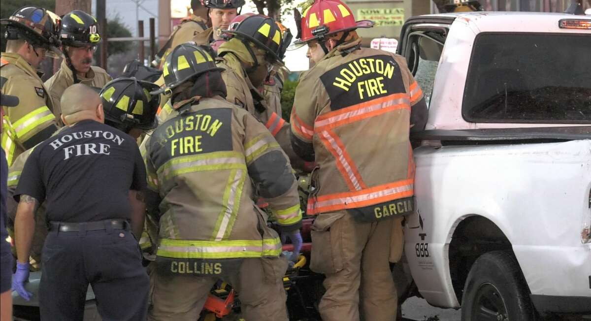 Houston firefighters work the scene where a driver who crashed into a utilty pole was trapped and freed from the car by rescuers Wednesday, Jan. 15, 2020.