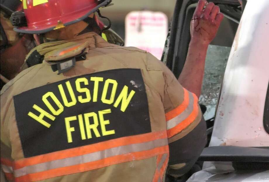 Houston firefighters work the scene where a driver who crashed into a utilty pole was trapped and freed from the car by rescuers Wednesday, Jan. 15, 2020. Photo: Jay R. Jordan / Houston Chronicle