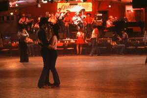 """CIRCA 1980: Actor John Travolta and Debra Winger dance at Gilley's in a scene during the Paramount Pictures movie 'Urban Cowboy"""" circa 1980. (Photo by Hulton Archive/Getty Images)"""