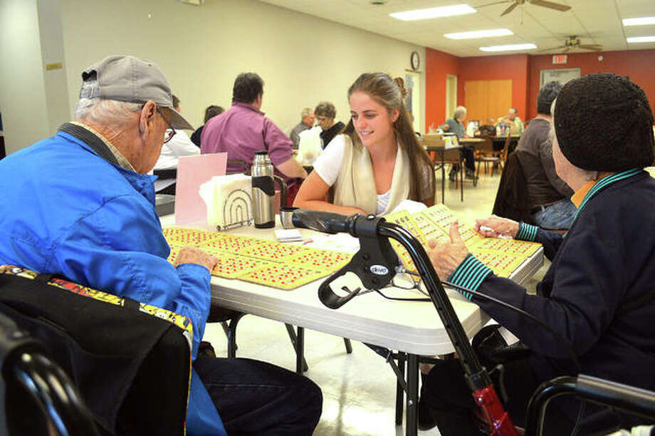 Caitlyn Orawiec, middle, talks to Main Street Community Center clients Milton, left, and Mary as they play bingo on Tuesday. Orawiec, a doctoral student in occupational therapy at Midwestern University in Chicago, will provide information to seniors about avoiding falls in their homes as an intern at Main Street Community Center during the spring semester. Photo: Scott Marion|The Intelligencer