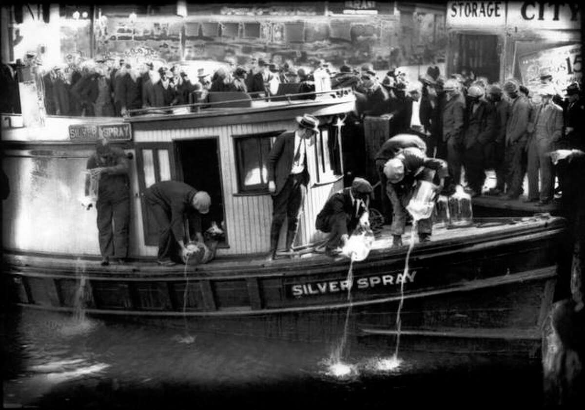 """In this 1922 file photo, spectators gather by the side of captured rum runner, Silver Spray, as they watch prohibition agents pour """"white lightning"""" from the five-gallon bottles on the deck into the Elizabeth River in Norfolk, Virginia. Charles S. Borjes 