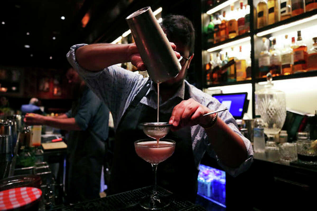 Mixologist Julian Bernal crafts a cocktail at Wink & Nod in Boston. Charles Krupa | AP