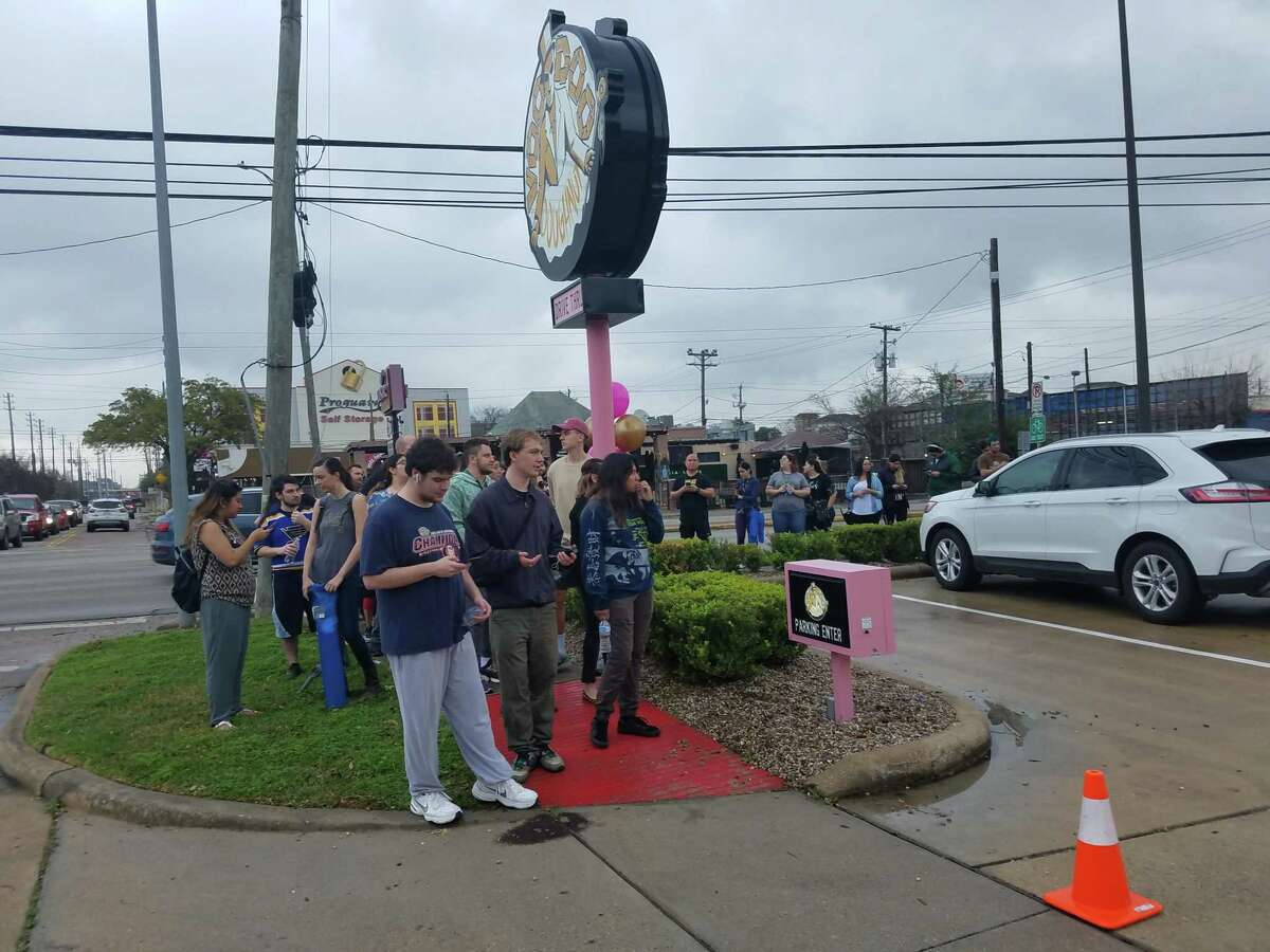Hundreds of customers wait in line for the grand opening of Voodoo Doughnut.