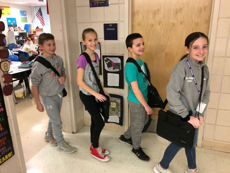 Perry Hill School students, left to right, Harrison Souza, Ava Pacacha, Andrew Aiello and Murphy Riddle carry their Chromebooks in their laptop bags. Photo: Brian Gioiele / Hearst Connecticut Media / Connecticut Post
