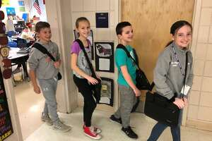 Perry Hill School students, left to right, Harrison Souza, Ava Pacacha, Andrew Aiello and Murphy Riddle carry their Chromebooks in their laptop bags.