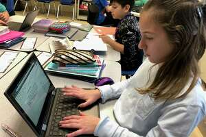Perry Hill School fifth graders Laney Graham and Derek Castanada do work on their Chromebooks.