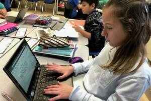 Perry Hill School fifth graders Laney Graham and Derek Castanada do work on their Chromebooks.