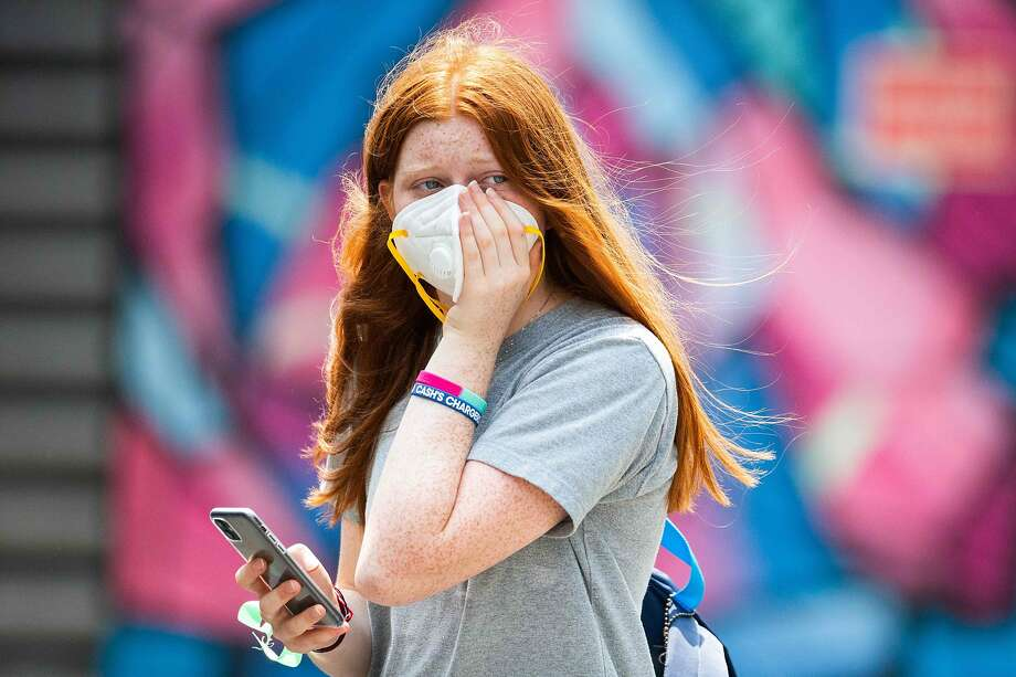 A woman holds her face mask in Melbourne, one of the world's most polluted cities in recent weeks. Photo: Asanka Brendon Ratnayake/ AFP Via Getty Images