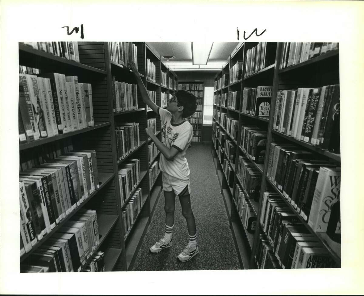 University City's 1st library. University City Library. Billy Tabb goes through books.