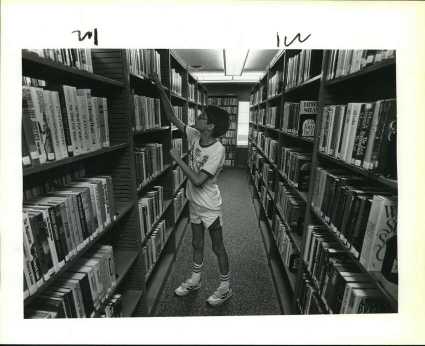 University City's 1st library. University City Library. Billy Tabb goes through books.