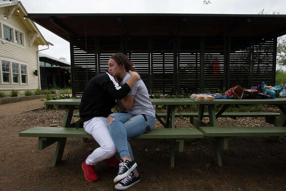 Bellaire High School students Emin Cruz, 16, and Grace Bandercan, 18, console each other at the gathering to remember the student who was shot and killed yesterday on campus at Evelyn Park on Wednesday, Jan. 15, 2020, in Bellaire.