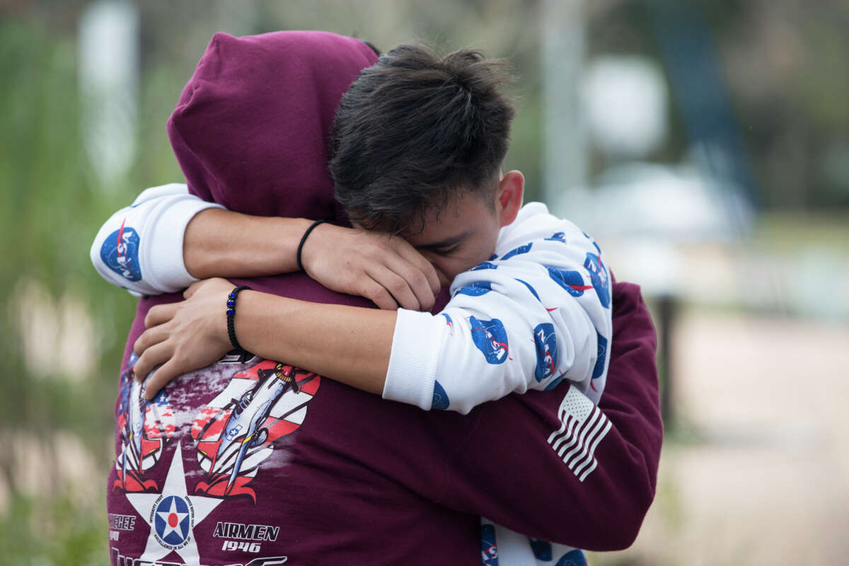 Bellaire High School students Viviana De La Torre, 17, and Adrian Interiano, 16, hug and console each other while gathering to remember the student who was shot and killed yesterday on campus at Evelyn Park on Wednesday, Jan. 15, 2020, in Bellaire.