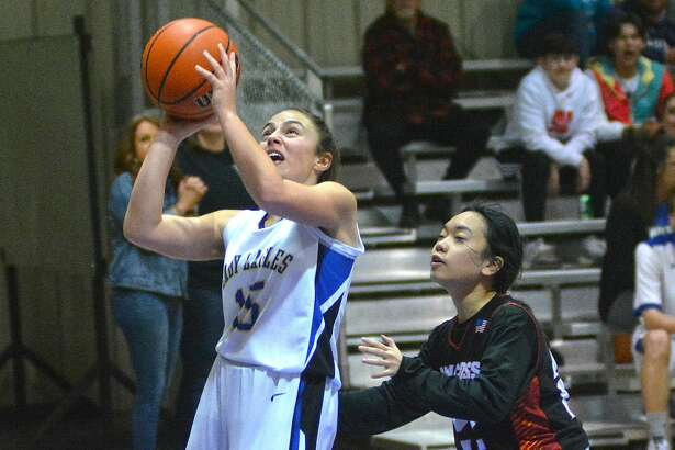 Plainview Christian Academy's Mia Stevens puts in the basket in front of a Holy Cross defender.