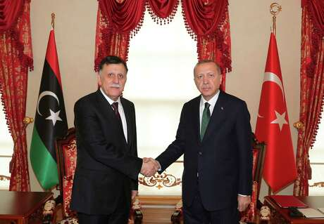 Turkey's President Recep Tayyip Erdogan, right, shakes hands with Fayez Sarraj, the head of Libya's internationally-recognized government, prior to their meeting in Istanbul.