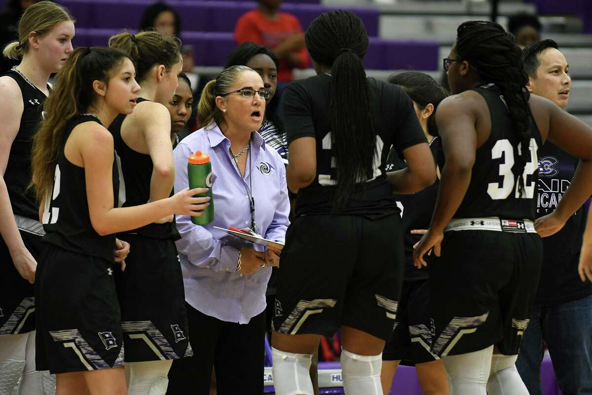 Klein Cain Head Girls Basketball Coach Melissa Fields, center, pumps up her team during a timeout against MacArthur during their non-district matchup at Klein Cain High School on Dec. 5, 2019.