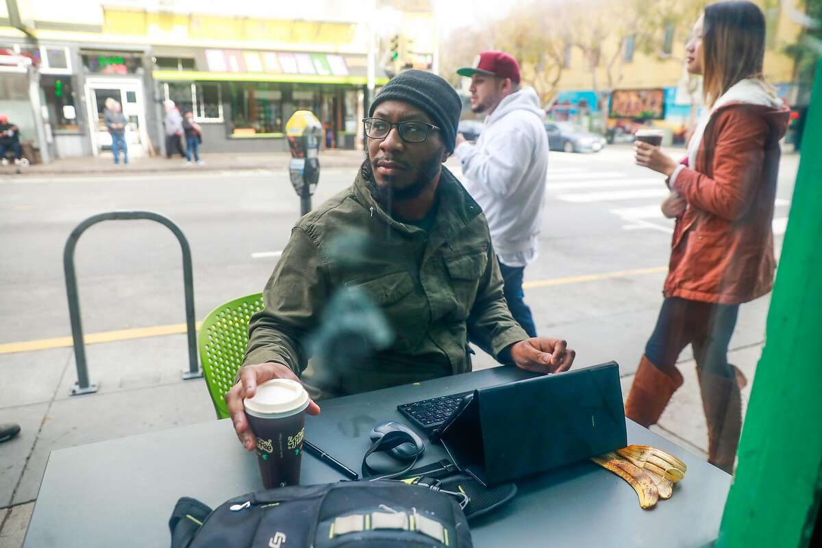 Brian Jones, of Boston, does work on his tablet outside of Philz coffee shop in the Mission on Wednesday, Jan. 15, 2020 in San Francisco, California.