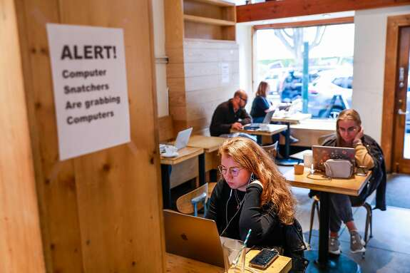 (L-r) Sofya Freeman and Katya Yetmolaieva sit beside a sign alerting them to laptop theft as they work on their laptops at Haus coffee shop in the Mission on Wednesday, Jan. 15, 2020 in San Francisco, California. Haus coffee experienced laptop theft from their shop about 7 months ago.
