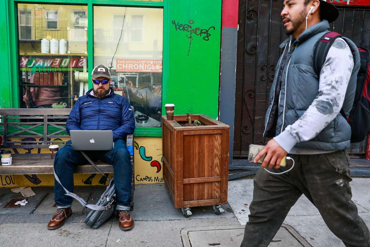 Damian Wisniewski (left) does work on his laptop outside of Philz coffee shop in the Mission on Wednesday, Jan. 15, 2020 in San Francisco, California.