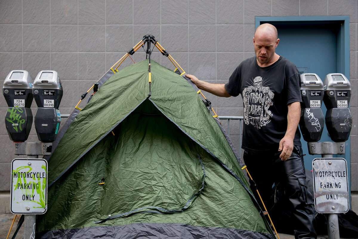Jason Clark, a homeless man, sets up his tent for the evening along Willow Street in San Francisco, Calif. Tuesday, Jan. 14, 2020.