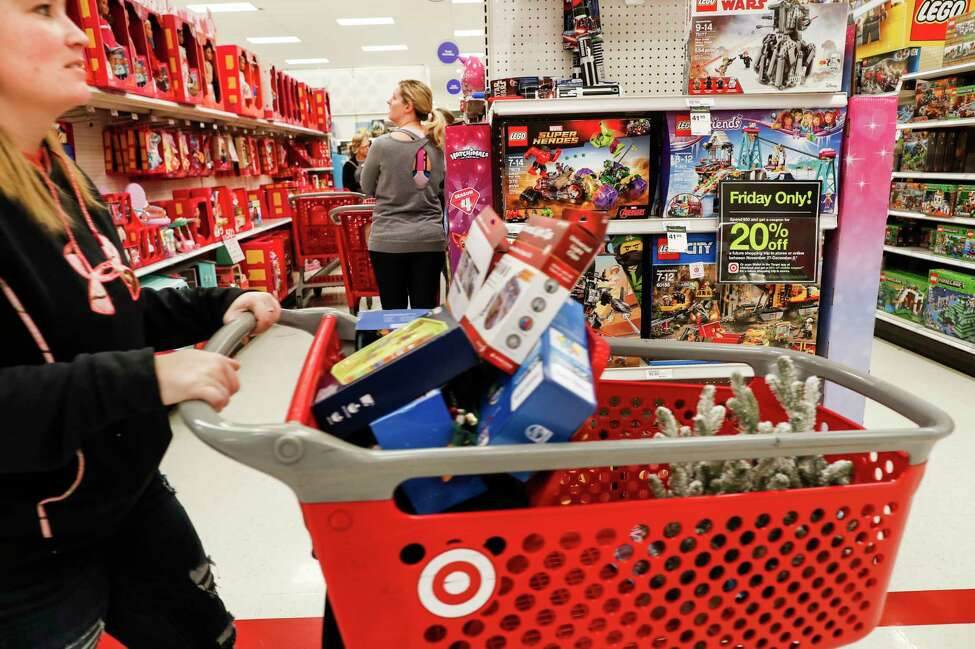 FILE- In this Nov. 23, 2018, file photo shoppers browse the aisles during a Black Friday sale at a Target store in Newport, Ky. Comparable stores sales at Target fell well below the previous year, joining a growing list of retailers reporting a meager performances during the critical holiday shopping season. Target said Wednesday, Jan. 15, 2020, that it had weaker-than-expected sales of electronics, toys and some home good. Those sales climbed 1.4% in the November-December period, compared with a 5.7% increase a year earlier. (AP Photo/John Minchillo, File)