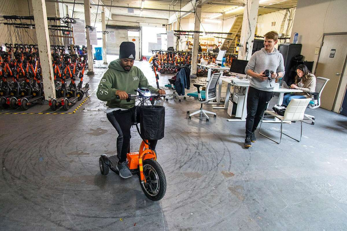 From left, Dre Cottrell and Kyle Merson-Wi look over a new three-wheeled accessibility scooter at Spin on Wednesday, Jan. 15, 2020 in San Francisco, Calif. Spin is one of the electric scooter companies that have rolled out new scooters designed for people with disabilities. The Spin model has three wheels and a seat.