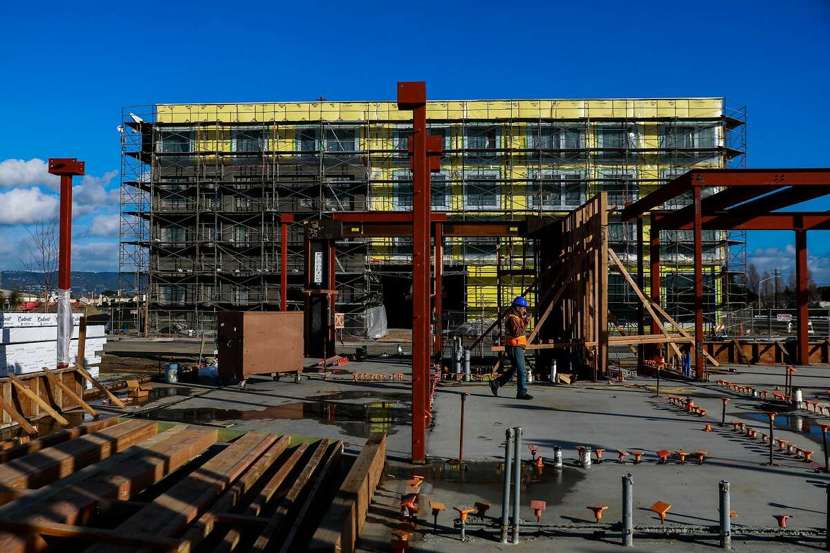 A construction worker walks past the site of a new condo under construction site at Alameda Point on Tuesday, Jan. 14, 2020 in Alameda, California.