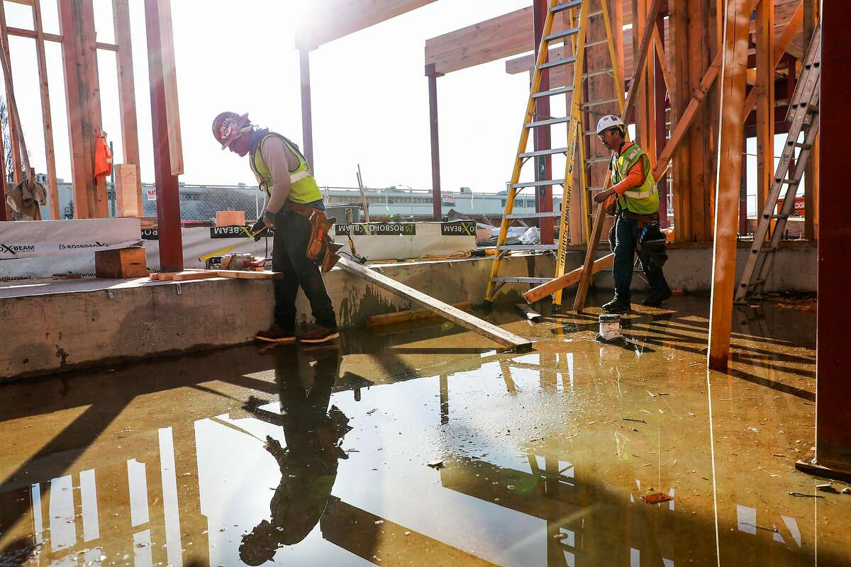 Valentin Gonzalez and Pedro Bonilla (right) work on a construction site that will be a new condo building at Alameda Point on Tuesday, Jan. 14, 2020 in Alameda, California.