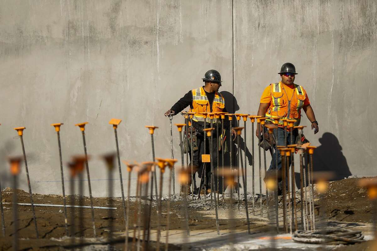 Construction workers walk through the foundation of a condo building they are working to build on Yerba Buena Island on Tuesday, Jan. 14, 2020 in San Francisco, California.