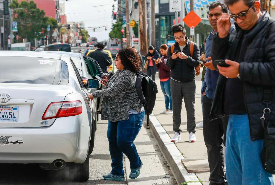 A woman hops into a ridesharing car while others wait for their transportation outside the Cal Train station on Townsend Street in San Francisco. Photo: Gabrielle Lurie / The Chronicle