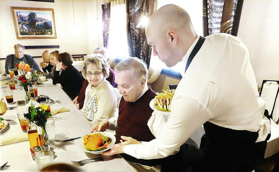 A server delivers food at lunchtime Wednesday to a large table of guests at Santino's Steak and Pasta House, 180 East Center Driver in Alton. The popular eatery will be participating in Restaurant Week, which begins Friday. A total of 25 local restaurants are participating in the annual event.