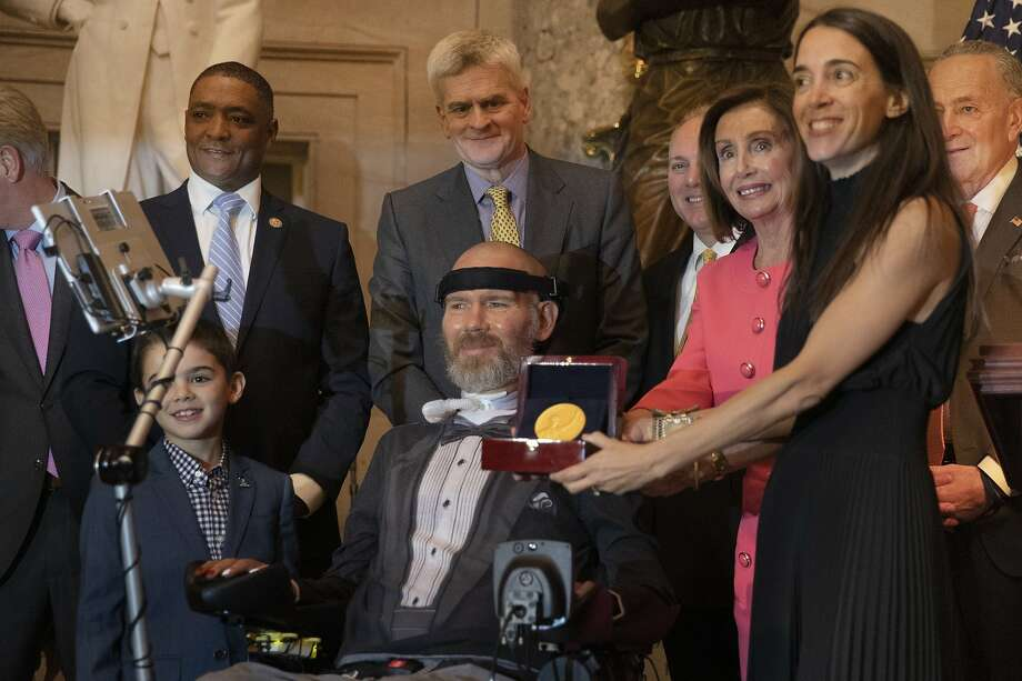 House Speaker Nancy Pelosi presents a Congressional Gold Medal to presented to Steve Gleason on Capitol Hill Wednesday. Assisting Pelosi is Gleason's wife, Michel. Photo: Manuel Balce Ceneta / Associated Press