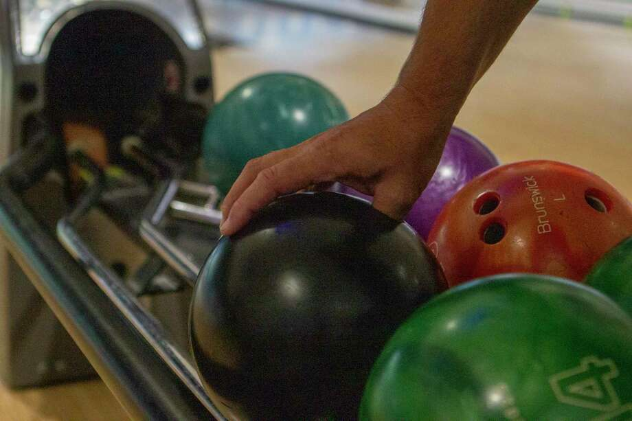 A bowler picks up his ball during the Racking Up Dollars for Scholars bowling tournament Saturday, July 20, 2019 at Time to Spare Entertainment in Cut and Shoot. Photo: Cody Bahn / Cody Bahn/Houston Chronicle / © 2019 Houston Chronicle