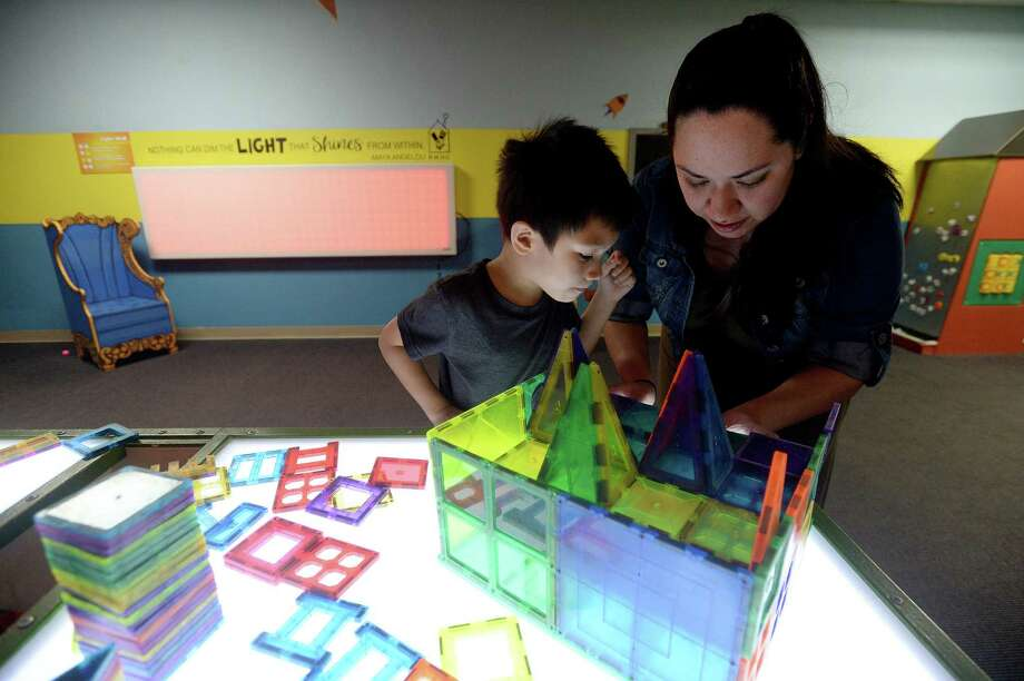 Jessalin Taing helps her son Kevin Taing as he creates a structure from magnetic shapes as the family spends the afternoon at the Beaumont Children's Museum Tuesday. City council discussed Tuesday the possible move of the museum into the former Sears warehouse on Magnolia Street, which the city has owned and used for storage for several years. The move would double their programming and on-site storage capabilities.  Photo taken Tuesday, Jan. 14, 2020 Kim Brent/The Enterprise Photo: Kim Brent / The Enterprise / BEN