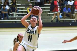 Reagan's Samantha Wagner (11) drives to the basket as Mariela Taylor (3) of Roosevelt attempts to defend during a battle of undefeated teams in District 27-6A.