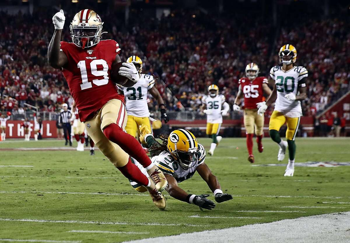 SANTA CLARA, CALIFORNIA - NOVEMBER 24: Wide receiver Deebo Samuel #19 of the San Francisco 49ers carries the ball to the endzone for a touchdown after making a catch during the first half of the game against the Green Bay Packers at Levi's Stadium on Nov