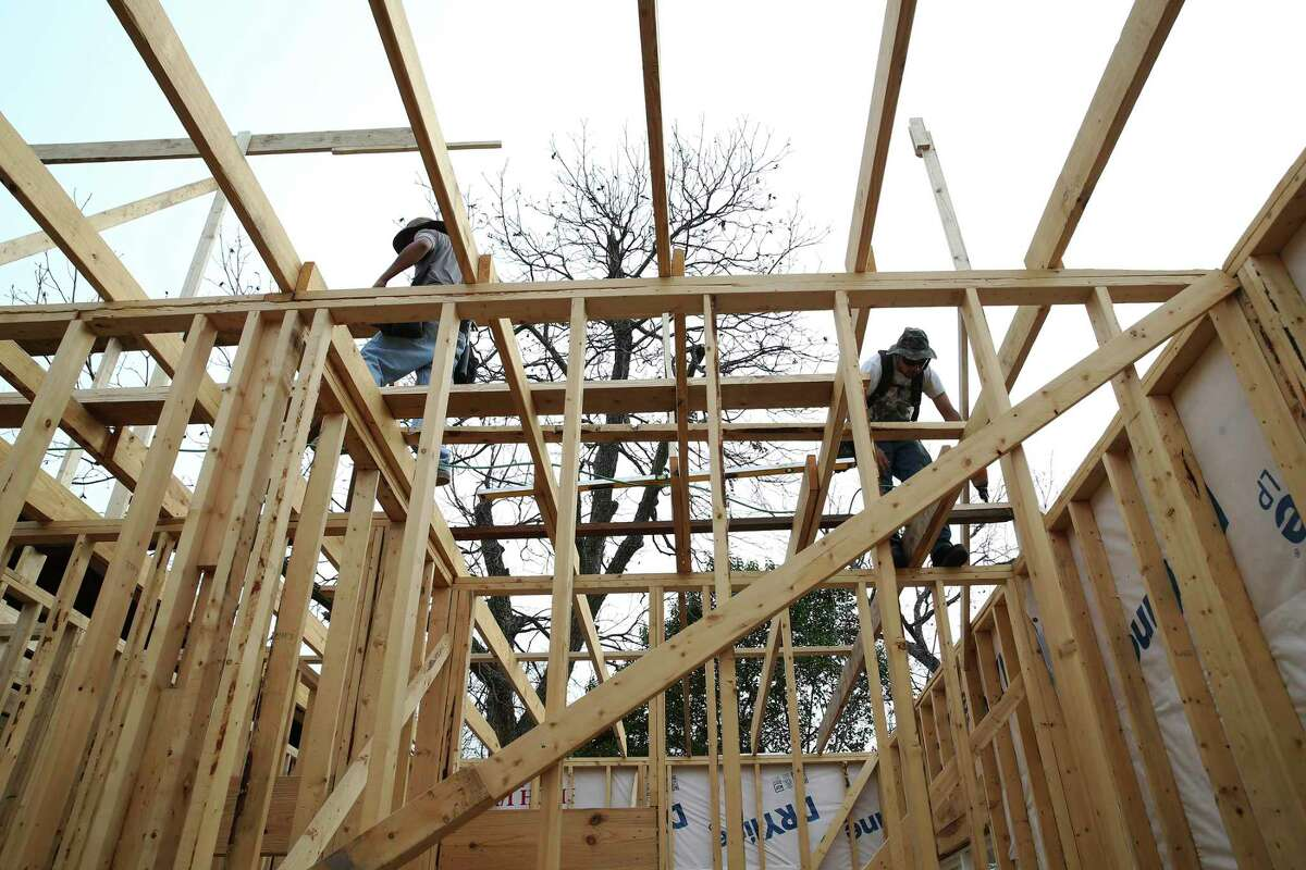 Ramiro Rodriguez, left, and Juan Rodriguez work on constructing a roof on a house on the 300 block of Spruce in Denver Heights on Wednesday, Jan. 15, 2020.