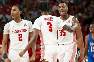Houston Cougars guard Caleb Mills (2), guard DeJon Jarreau (3) and forward Fabian White Jr. (35) celebrate after a play during the second half of the Cougars' game against the Mustangs at the Fertitta Center in Houston, Wednesday, Jan. 15, 2020.