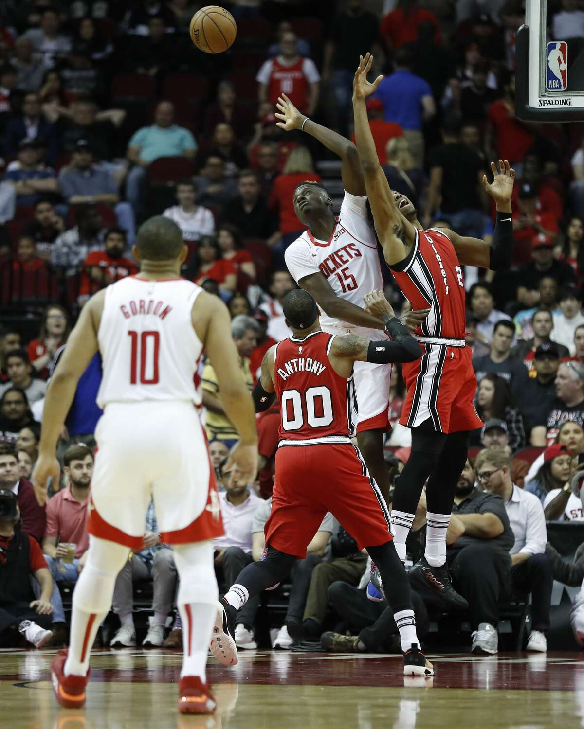 Houston Rockets center Clint Capela (15) reaches for a rebound against Portland Trail Blazers guard Gary Trent Jr. (2) and forward Carmelo Anthony (00) in the second half of an NBA basketball game at Toyota Center, in Houston, Wednesday, Jan. 15, 2020.