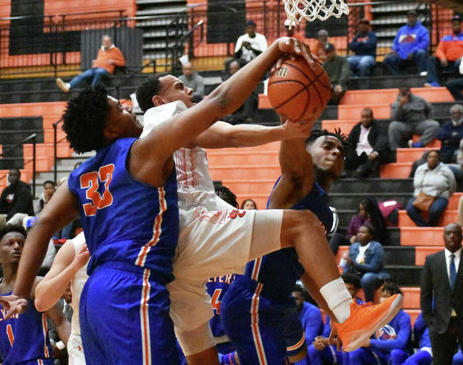 Edwardsville guard Ethan Young has his shot blocked by two East St. Louis Flyers in the first quarter Wednesday inside Lucco-Jackson Gymnasium. Photo: Matt Kamp|The Intelligencer