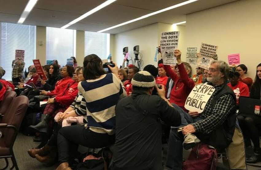 Protesters rise up at a state Public Service Commission meeting where electric and gas hikes were approved by Con Edison.
