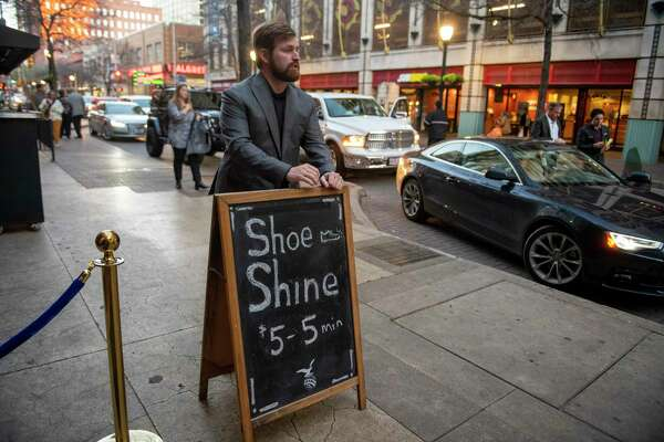 Standing vigil by his sandwich sign, Craig Berkenkamp lures downtown denizens into his shop for a shine that starts at $5 for 5 minutes.