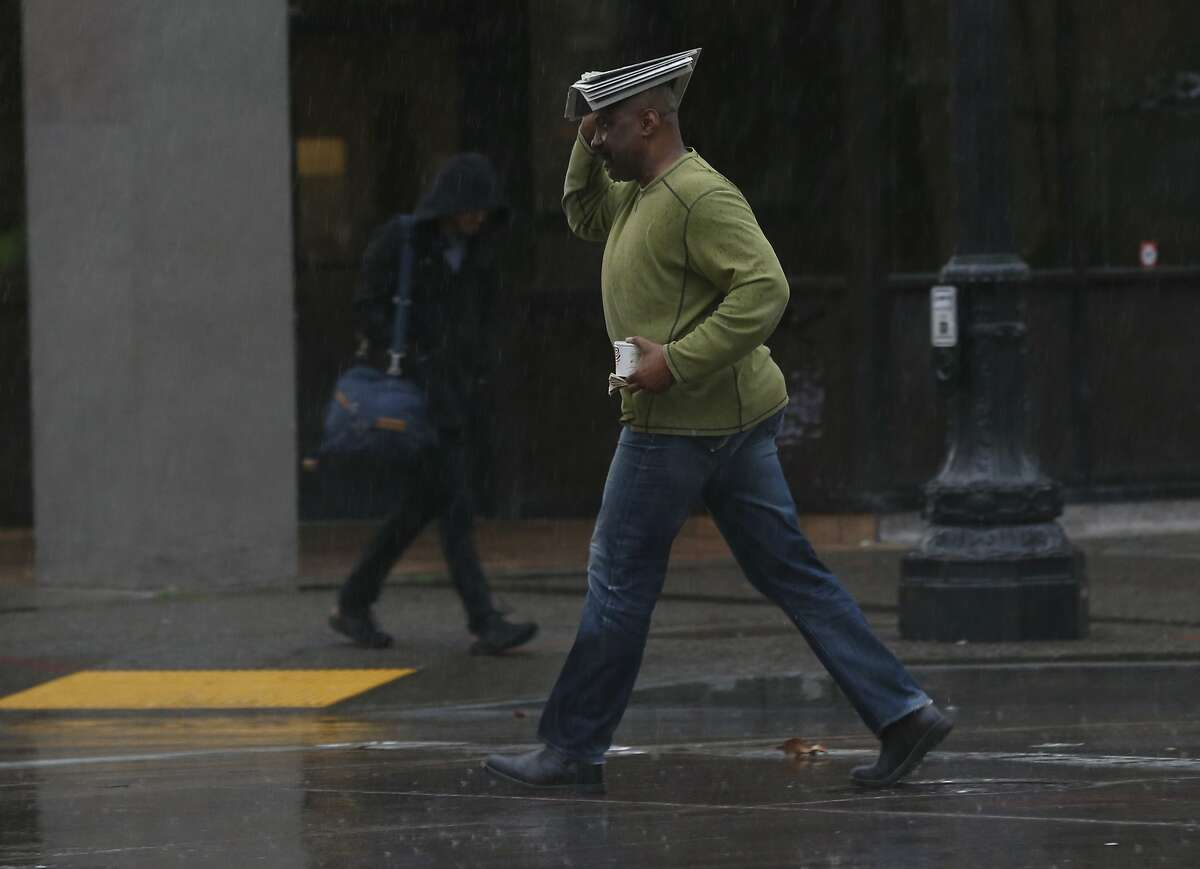 A man covers his head while crossing Broadway as heavy rain drenches the area in Oakland, Calif. on Thursday, Jan. 16, 2020.