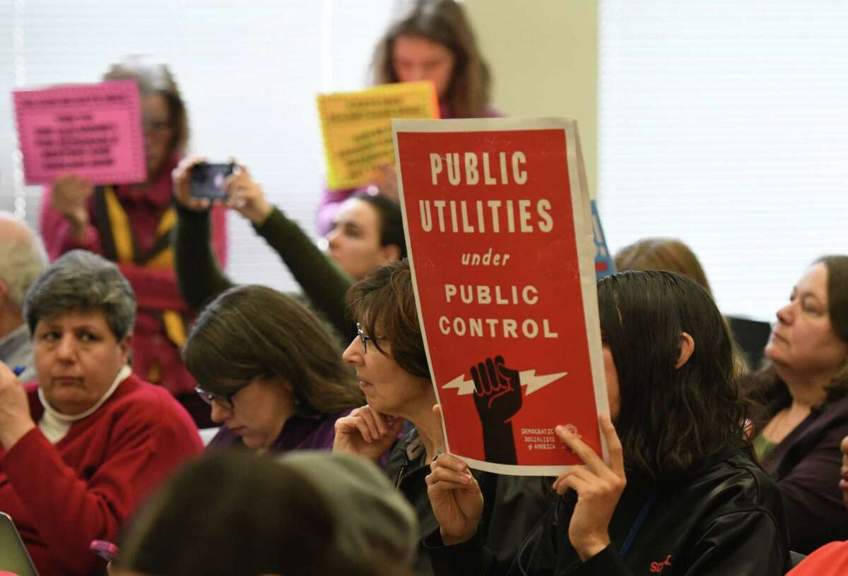 Protesters raised signs spoke out during a state Public Service Commission meeting where electric and gas hikes were approved by Con Edison on Thursday, Jan. 16, 2020, at Empire State Plaza Agency Building 3 in Albany, N.Y. (Will Waldron/Times Union)